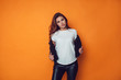 Leinwanddruck Bild Sexy woman in white t-shirt and jacket on the orange background. Mock-up.