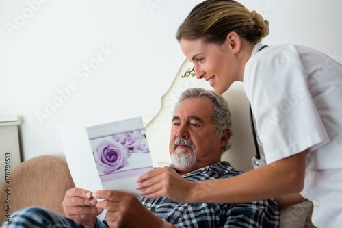 Valokuva Female doctor showing get well card to patient relaxing on bed