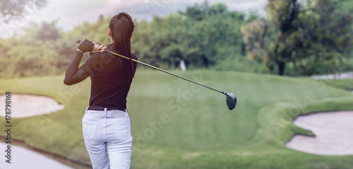 Foto auf Leinwand Golf Young women player golf swing shot on course