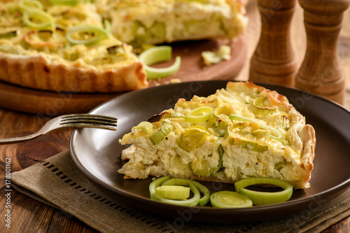Quiche with leek and cheese on brown background. Wallpaper Mural