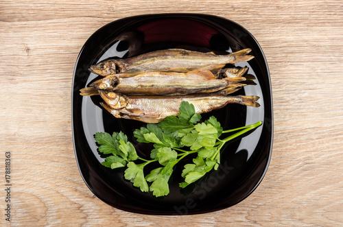 Fototapeta Uwędzony gromadnik i pietruszka w czarnym talerzu na drewnianym stole