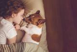 Fototapeta Zwierzęta - Sweet curly girl and jack russell dog is sleeping in night.