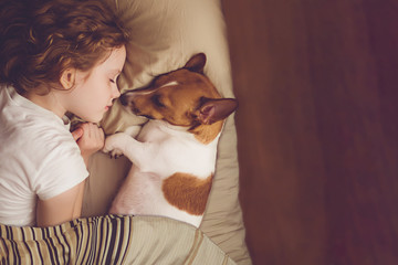 FototapetaSweet curly girl and jack russell dog is sleeping in night.