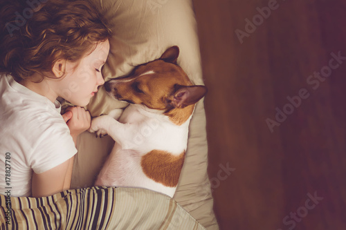 Photo  Sweet curly girl and jack russell dog is sleeping in night.