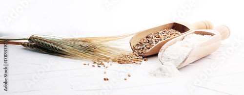 Fotografia Whole grain wheat flour and seeds on white background.