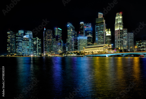MARINA BAY SANDS, SINGAPORE - May 23, 2017: Colorful Singapore City with hard black skyline on the bridge at night Marina Bay Sands Poster