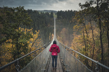 Young Woman On Geierlay Supsension Bridge, Germany, On A Cold Autumn Morning