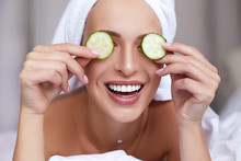 Young Beautiful Smiling Woman With Towel On Her Head Holding Cucumber Slices On The Face. Skin Care, Spa And Beauty Treatments. Anti Aging Cosmetics.