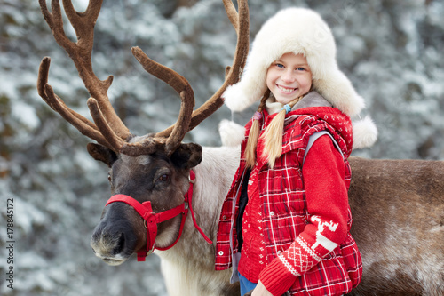 mata magnetyczna Winter playtime.Happy little girl hugging her reindeer.