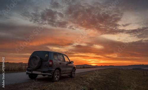 Plakat samochód na poboczu o zachodzie słońca