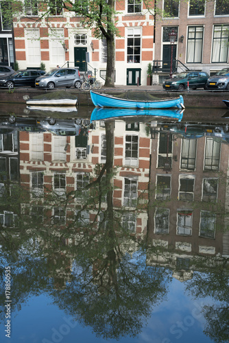 Photo  Reflection and blue boat in canals in Amsterdam