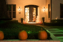 The House Is Decorated For Halloween: Pumpkins Are Real And Artificial, Skeletons On The Doors. Night