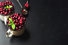 Fresh Red Cranberries With Mint Leaves In A White Cup And Spoons On A Dark Black Background With Copy Space.