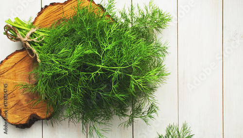 Photo sur Toile Condiment Fresh dill on a white wooden table top view. Fresh greens, seasoning, the process of cooking dishes, a healthy lifestyle.