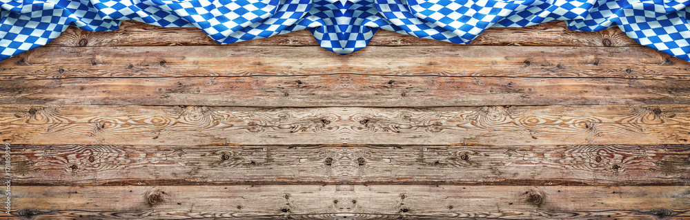 Rustic background for Oktoberfest with bavarian white and blue fabric on wooden
