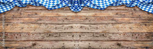 Fotografia Rustic background for Oktoberfest with bavarian white and blue fabric on wooden