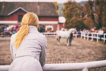 Blonde woman is watching a horse auction, English thoroughbred on a show