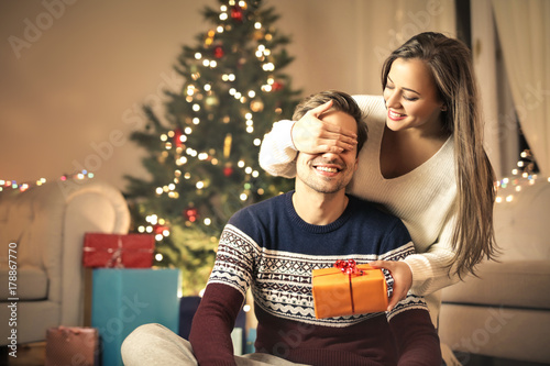 Sweet girl giving a Christmas gift to her boyfriend Fotobehang
