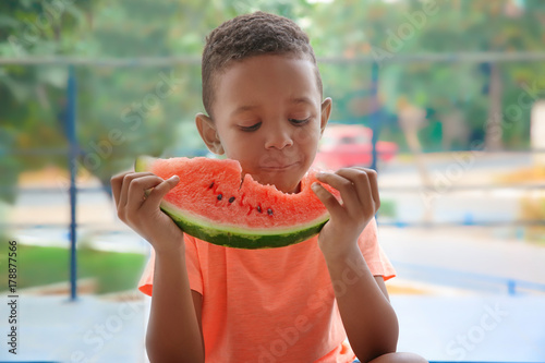 Cute African American boy eating watermelon at home