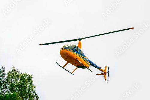 Tuinposter Helicopter Yellow helicopter down into the forest. Air transport in the sky. Useful aircraft helicopters. Aircraft emergency help.