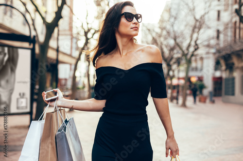 Fotografía  Beautiful female walking on the street with shopping bags