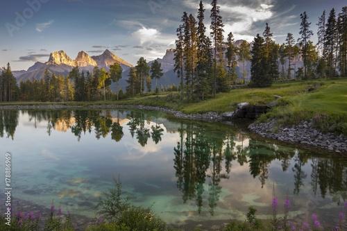 Plakat Refleksje nad jeziorem w słynnym polu golfowym Silvertip nad miastem Canmore z odległym krajobrazem Widok z góry trzy siostry w Alberta Pogórze w pobliżu Parku Narodowego Banff