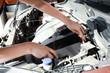 Young female mechanic repairing car in body shop