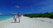 v12618 two 2 people walking romantic young people couple holding hands on a tropical island of white sand beach and blue sky and sea