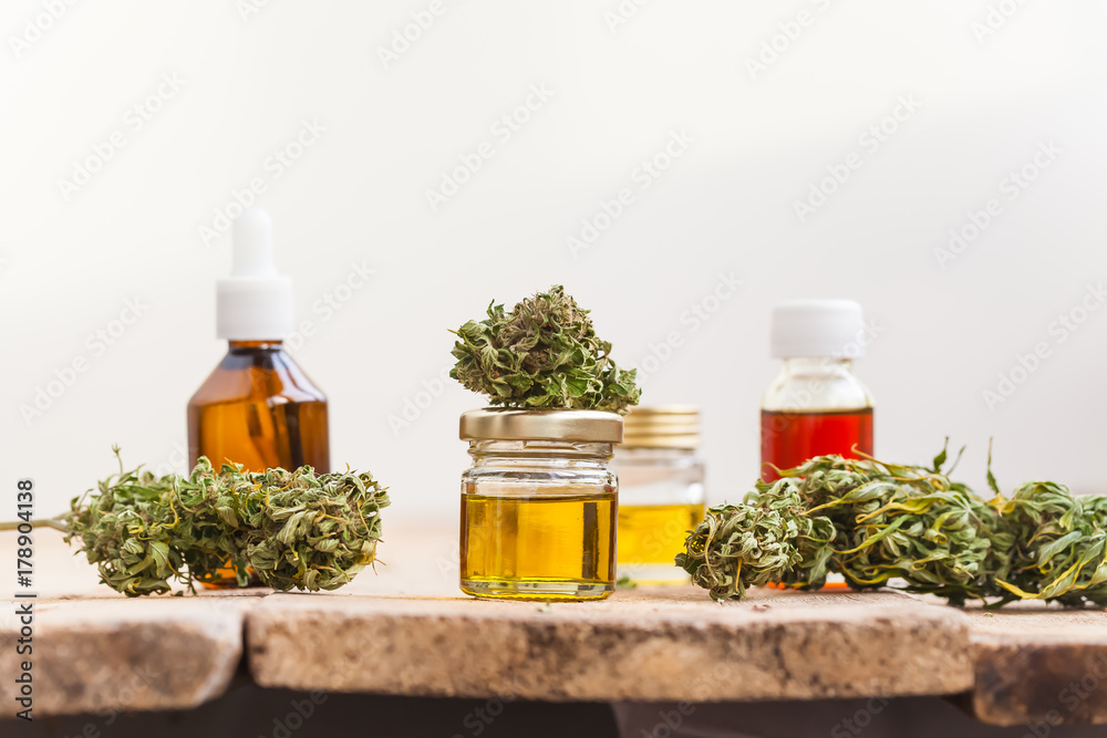 Fototapety, obrazy: alternative medicine green leaves of medicinal cannabis with extract oil on a wooden table