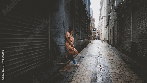 Lifestyle full portrait of young attractive fashionable Caucasian female in a coat standing in the narrow street in Europe. Horizontal orientation