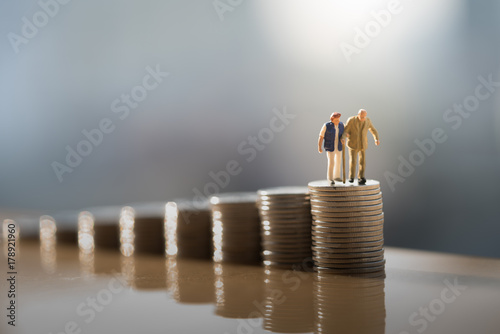 Fototapeta Concept of retirement planning. Miniature people: Old couple figure standing on top of coin stack. obraz