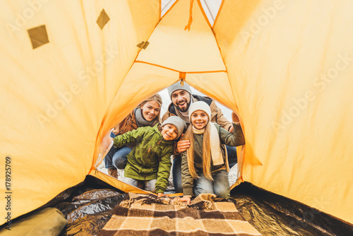 Poster Kamperen family looking at camping tent