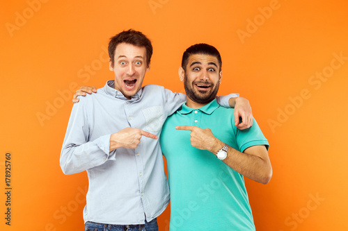 Photo  Two best friends hugging, pointing finger each other and looking at camera with