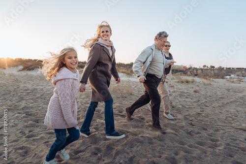 Poster Artist KB multigenerational family walking on beach
