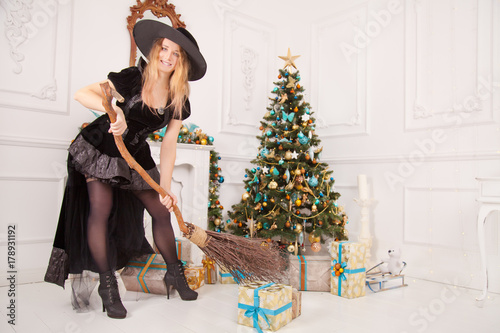 Valokuva  pretty cute evil witch wearing long black velvet dress destroy christmas