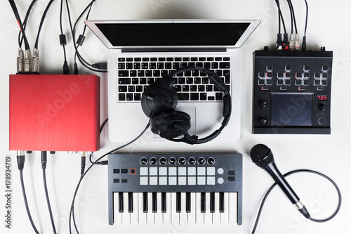 Portable and compact music home studio for electronic and beat music production. Top view of modern music recording set up with professional headphones, software controllers, digital effect processors - 178934719