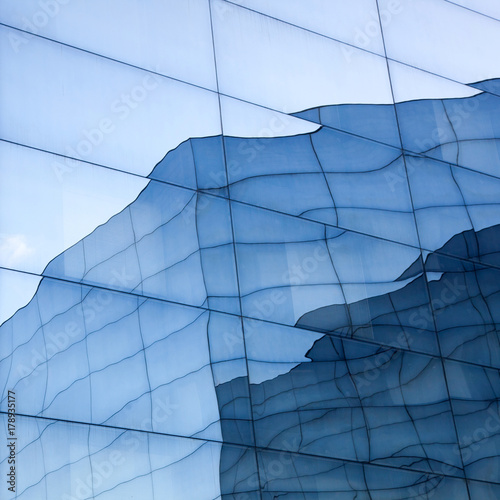 Photo sur Toile Les Textures part of geometrically shaped modern glass building with reflections of blue sky and glass wall