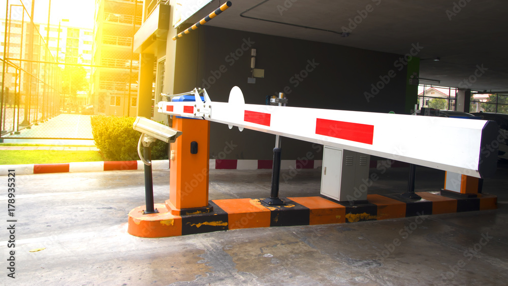 Fototapeta Security system for building access - barrier gate stop with toll booth, traffic cones and cctv.