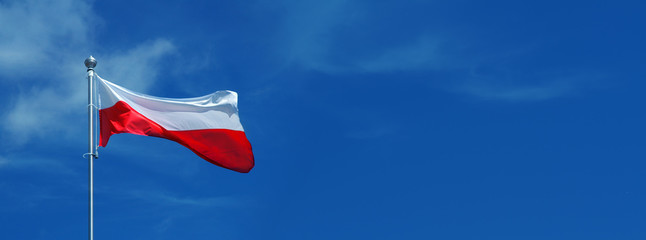 Polish, white and red flag waving against the blue sky