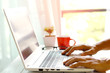 Man's hands using laptop with blank screen on desk in home interior.