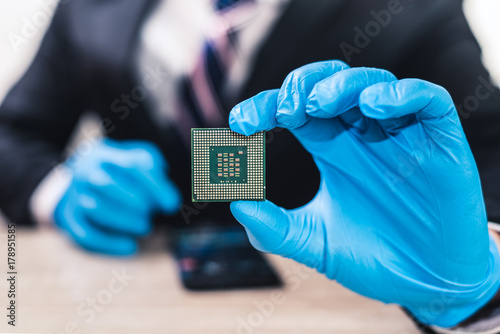 The abstract image of the business man wear a gloves and hold a CPU chip. the concept of business, technology, hardware, jobs, and electronics.