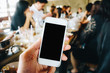 Blank cellphone screen in hand blurred people background in restaurant
