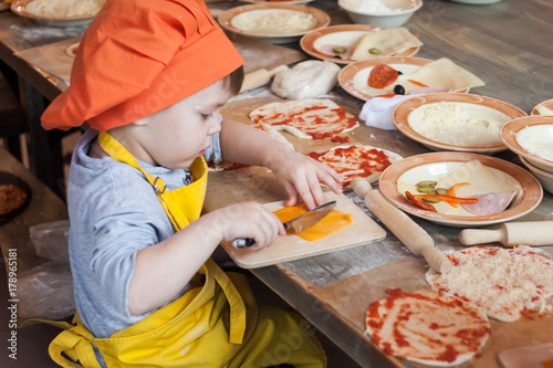 Foto op Plexiglas Koken Little cook. Children make pizza. Master class for children on cooking Italian pizza. Young children learn to cook a pizza. Kids preparing homemade pizza