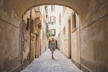 Full Length Of Woman Walking In Narrow Footpath Amidst Buildings