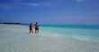 v12669 two 2 people walking romantic young people couple holding hands on a tropical island of white sand beach and blue sky and sea