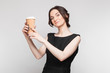 Picture of beautiful woman in black dress with coffe in hands
