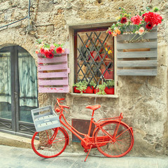 Fototapeta na wymiar Red bike in a traditional Italian medieval town, Tuscany, Italy.