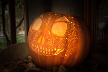 Artistically Carved Glowing Jack-o'-lantern On Tabletop Display With Leaves For Hallowe'en