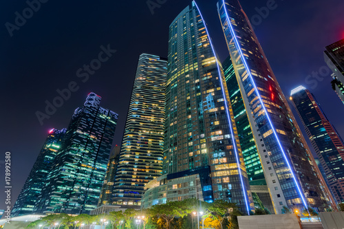 Obraz Bottom view to skyscrapers at downtown district. Singapore at night - fototapety do salonu