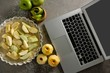 Laptop with apple tart and peeled green apple